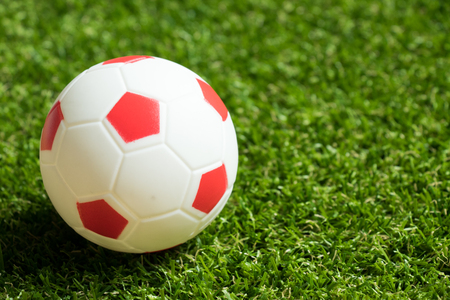 winning pitch: Toy red and white color football on artificial green grass background