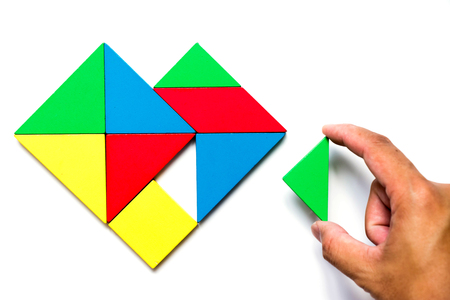 Colorful wooden tangram puzzle in heart shape wait to fulfill with triangle shape on white background Stock Photo