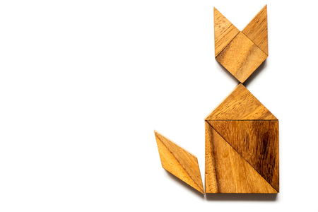 moggy: Wood tangram puzzle in cat sitting shape on white background