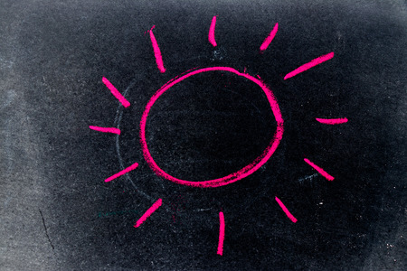Red chalk drawing as sun with ray on black board background