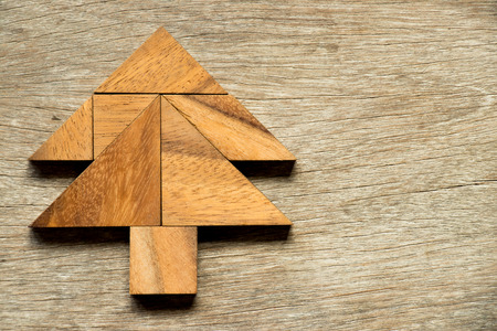 jigsaw tangram: Tangram puzzle in christmas tree shape on wood background