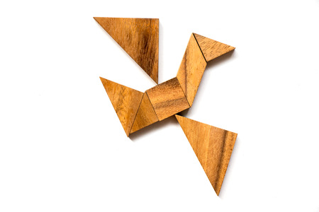 Wooden tangram puzzle in flying bird shape on white background (Concept of business start up or entrepreneur)
