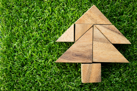 Wood tangram puzzle in Christmas tree shape on artificial green grass background