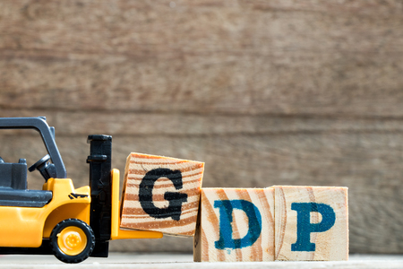 Toy plastic forklift hold block G to compose and fulfill wording GDP (Gross domestic product or Good distribution practice) on wood background Stock Photo