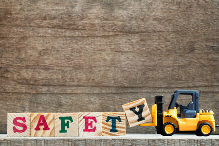 Toy plastic forklift hold block Y to compose and fulfill wording safety on wood background Stock Photo