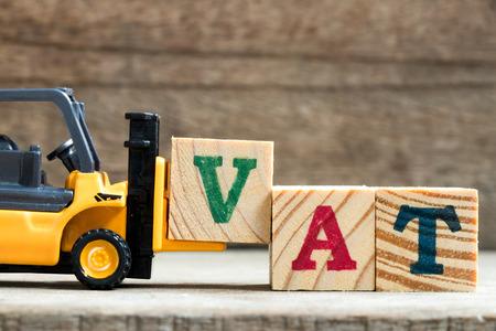 Plastic speelgoedvorkheftruck houdt blok V vast om te formuleren en te voldoen aan de formulering BTW Stockfoto