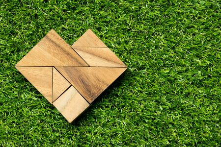 jigsaw tangram: Wood tangram puzzle in heart shape on artificial green grass background