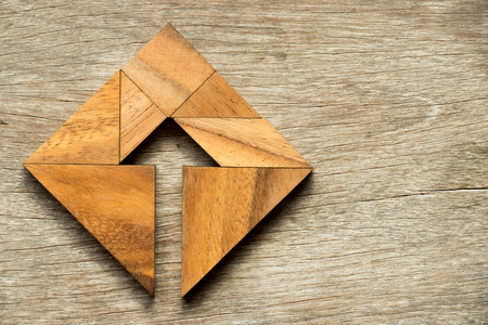 Tangram puzzle in square shape with the arrow symbol inside on wood background Archivio Fotografico