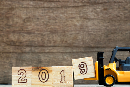 Toy plastic forklift hold block to compose and fulfill wording 2019 on wood background Foto de archivo