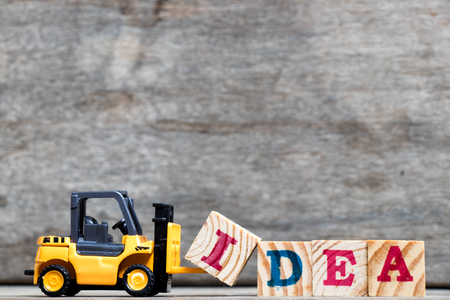 Yellow plastic forklift hold letter I to complete word idea on wood background