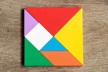 Colorful tangram puzzle in square shape on wood background