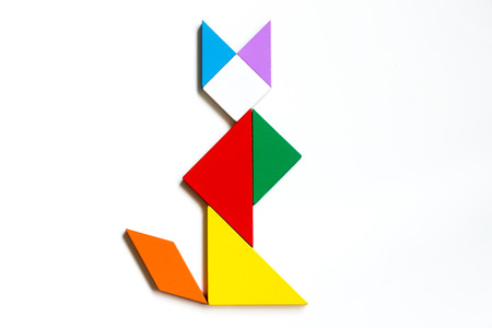 jigsaw tangram: Colorful wood tangram puzzle in sitting cat shape on white background