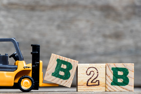 Yellow plastic forklift hold letter B to complete word B2B (Business to business) on wood background