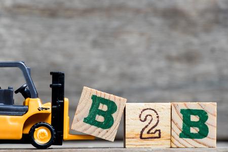 Gelber Plastikgabelstaplergriffbuchstabe B, zum des Wortes B2B (Geschäft zum Geschäft) auf hölzernem Hintergrund zu vervollständigen Standard-Bild