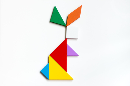 jigsaw tangram: Colorful wood tangram puzzle in sitting rabbit shape on white background
