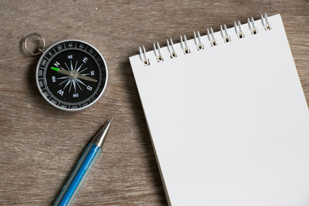 Blank note paper with compass on wood desk background