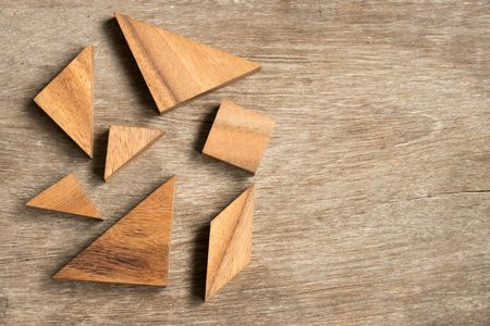 jigsaw tangram: Straggled tangram puzzle  wait to complete the shape on wood background