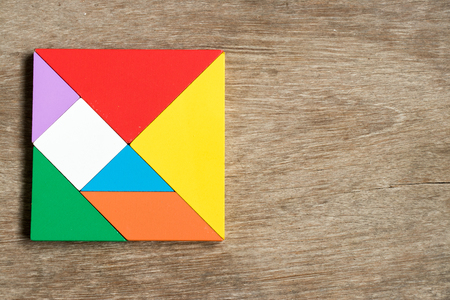 jigsaw tangram: Colorful tangram puzzle in square shape on wood background