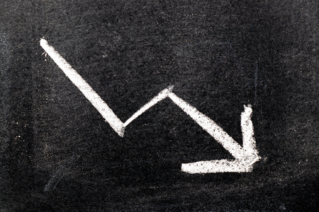 White color hand drawing chalk in arrow down shape on black board background (Concept of stock decline, down trend of business, economy) Foto de archivo