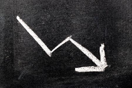 Tiza de dibujo a mano de color blanco en forma de flecha hacia abajo sobre fondo de tablero negro (Concepto de disminución de stock, tendencia a la baja de negocios, economía)