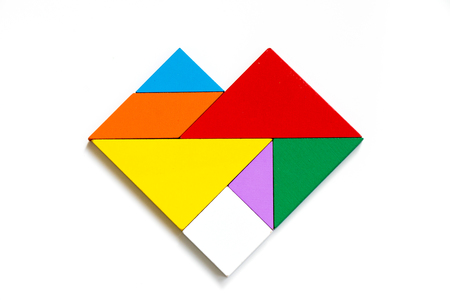 Colorful wood tangram puzzle in heart shape on white background