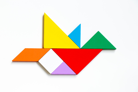 Colorful wood tangram puzzle in flying bird shape on white background