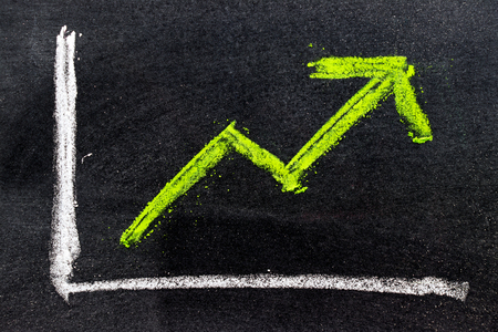 Green color hand drawing chalk in arrow up shape on black board background (Concept of revenue increase, stock or business growth) Stock Photo