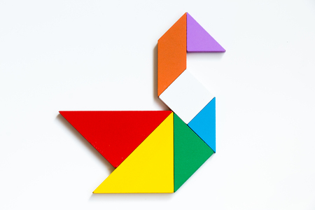 Colorful wood tangram puzzle in swan shape on white background