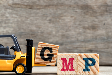 Yellow plastic forklift hold letter G to complete word GMP (Abbreviation of Good Manufacturinc Practice) on wood background Stock Photo
