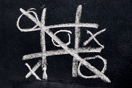 White chalk drawing as Tic Tac Toe with the winner and loser shape on black board background Stok Fotoğraf