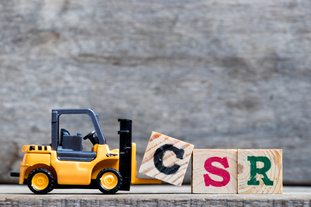 Yellow plastic forklift hold letter C to complete word CSR (Abbreviation from corporate social responsibility) on wood background  Stock Photo