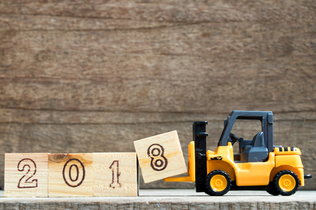 Toy plastic forklift hold block to compose and fulfill wording 2018 on wood background