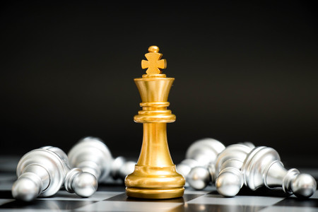 Gold king in chess game face with the another silver team on black background (Concept for company strategy, business victory or decision) 免版税图像