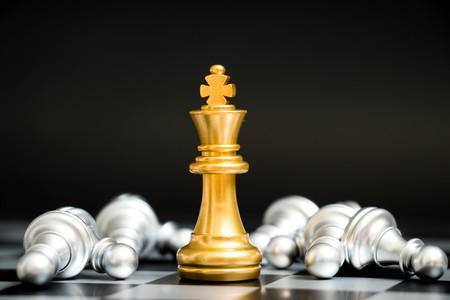 Goldkönig im Schachspielgesicht mit dem anderen silbernen Team auf schwarzem Hintergrund (Konzept für Firmenstrategie, Geschäftssieg oder Entscheidung)