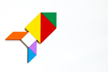 Colorful wood tangram puzzle in rocket or missile shape on white background
