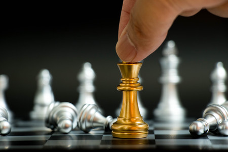 Businessman hold gold king with silver pawn lay down in chess game on black background (Concept for vitory in business, leadership) 写真素材