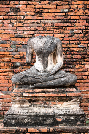 Ancient broken buddha statue with red brick background in temple at Ayutthaya, Thailand