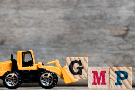 Yellow plastic bulldozer hold letter G to complete word GMP (Abbreviation of Good Manufacturinc Practice) on wood background