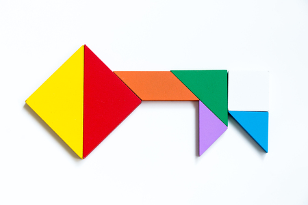 colorful wood tangram puzzle in key shape on white background photo
