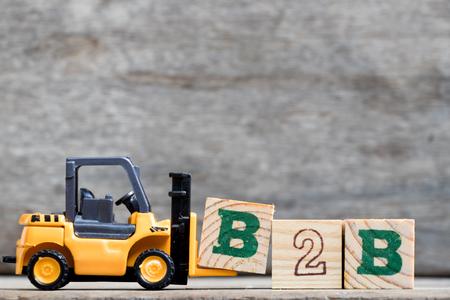 Gelber Plastikgabelstaplergriffbuchstabe B, zum des Wortes B2B (Geschäft zum Geschäft) auf hölzernem Hintergrund zu vervollständigen Standard-Bild - 90780564
