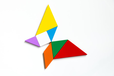 Colorful wood tangram puzzle in butterfly shape on white background 스톡 콘텐츠