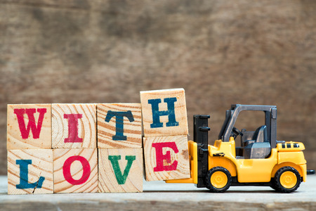 Yellow toy forklift hold letter block H and E to complete word with love on wood background Standard-Bild