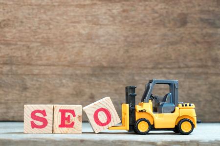 노란색 장난감 지게차 문자 블록 O 나무 배경에 word SEO (검색 엔진 최적화의 약어)를 완료하려면 개최