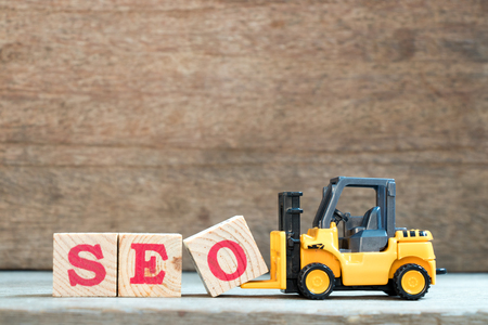 Yellow toy forklift hold letter block O to complete word SEO (Abbreviation of search engine optimization) on wood background Standard-Bild