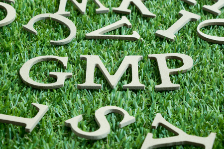 Wood letter in word GMP (Abbreviation from Good manufacturing practice) on artificial green grass wit English alphabet background Stock Photo