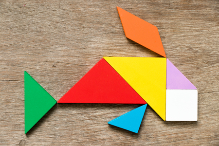 Colorful tangram puzzle in swimming fish or carp shape on wood background