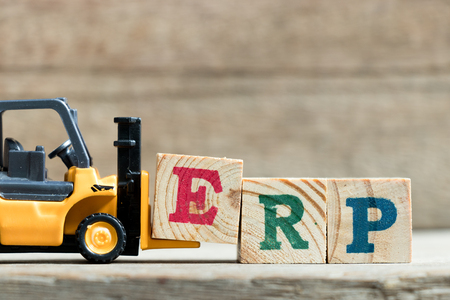 Toy yellow forklift hold letter block E to complete word ERP (Abbreviation of Enterprise Resource Planning)on wood background Stock Photo