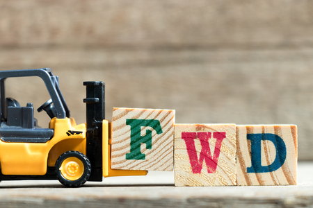 Toy yellow forklift hold letter block F to complete word FWD (Abbreviation of forward)on wood background