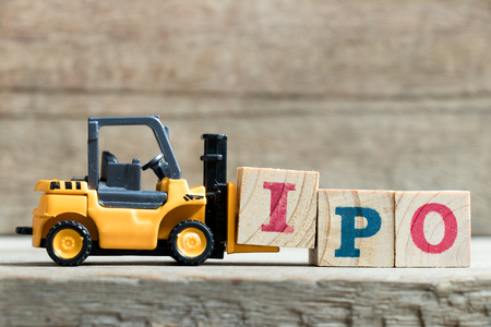 Toy yellow forklift hold letter block I to complete word IPO (Abbreviation of Initial Public Offering)on wood background