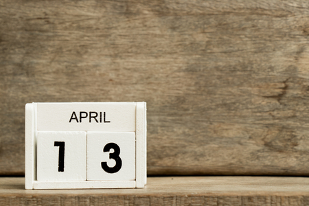 White block calendar present date 13 and month April on wood background